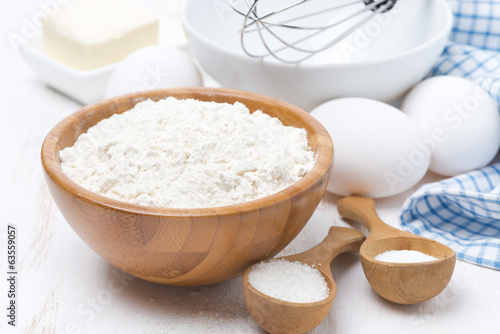 flour, salt, sugar and eggs for baking pancakes on wooden table