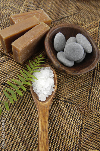 Soaps and stones in bowl and fern with salt in spoon