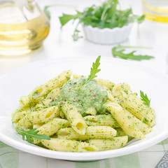 pasta penne with sauce of arugula and peas, close-up