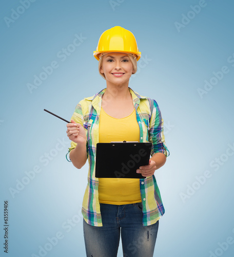 smiling woman in helmet with clipboard