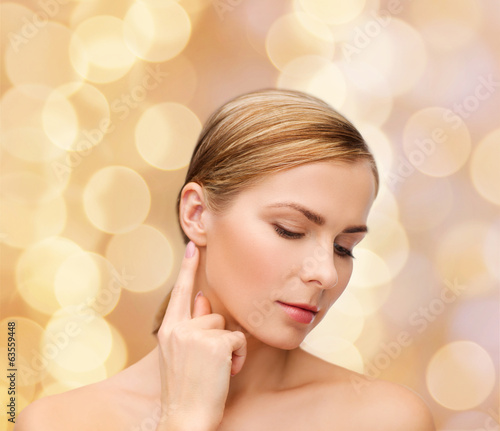 calm woman touching her ear