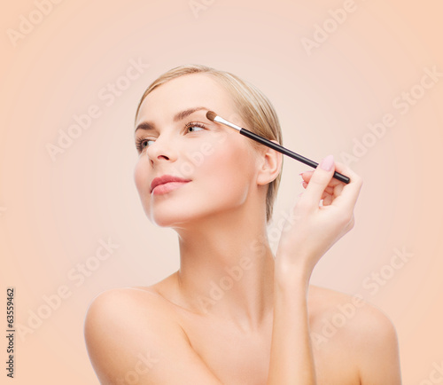 beautiful woman with makeup brush