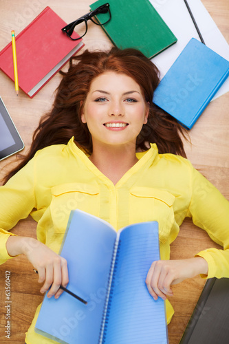 smiling female student with textbook and pencil