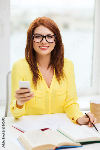 smiling student girl with smartphone at school
