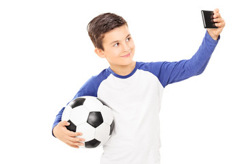 Boy holding football and taking a selfie