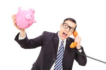Angry businessman holding an empty piggybank