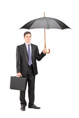 Man holding an umbrella and a briefcase