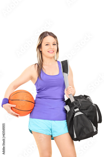 Woman holding basketball and a sports bag