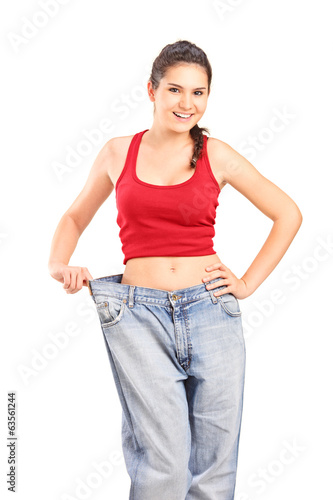 Girl showing her old, oversized pair of jeans