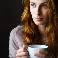 Beautiful and relaxed girl drinking tea