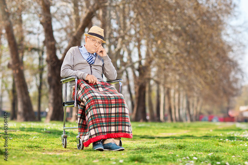Grumpy old man sitting in a wheelchair in park