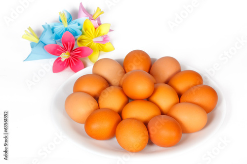 Easter eggs on the plate with colored paper flowers