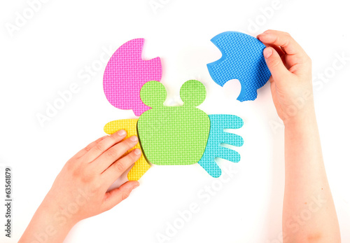 Hand and multicolored foam puzzle
