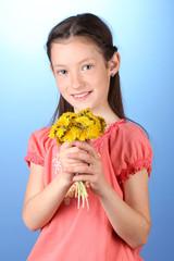 Portrait of beautiful little girl with dandelions