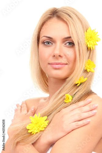 Beautiful young woman with a bright yellow chrysanthemums in