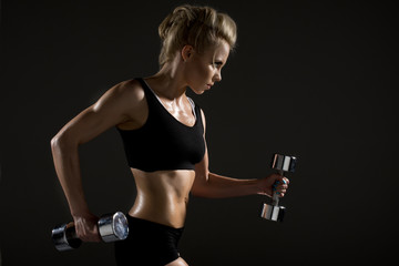 Sexy woman doing physical exercise with dumbbells