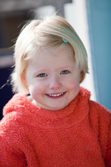 Beautfiul little blond girl with a cheerful smile