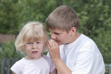Дети. Мальчик шепчет секрет на ухо