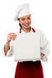 Smiling female chef opening pizza box