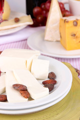 Assorted cheese plate on pink tablecloth background, close-up