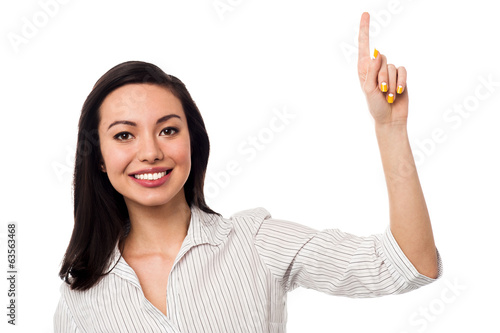 Smiling girl pointing upwards