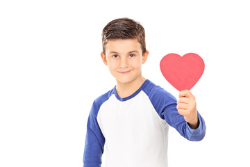Young boy holding a red heart