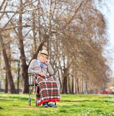 Worried senior sitting in a wheelchair in park