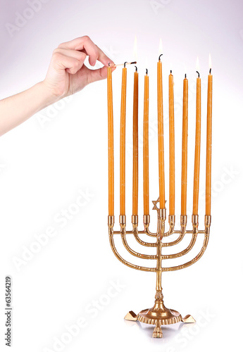 Hand ignites candles isolated on white