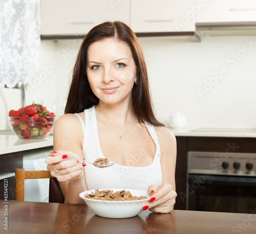 girl having breakfast in  kitchen.