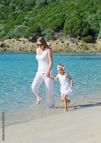 Mother and daughter having fun near the sea.