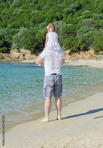 Man with daughter on shoulders standing on the beach.