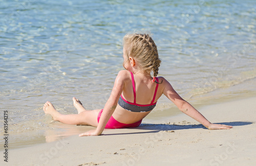 Little girl relaxing near the ocean.