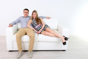 Loving couple sitting on sofa, on light background