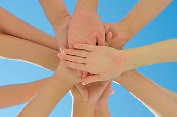 Many hands together over blue sky.