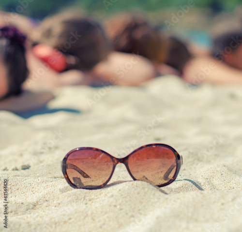 Sunglasses on the background of people sunbathing on the beach