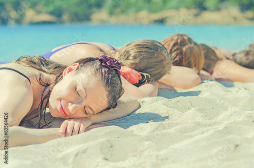 Company of girls sunbathing on the beach.