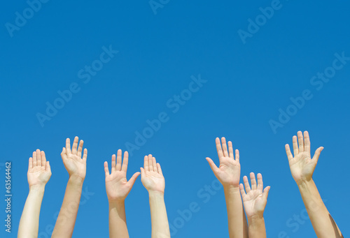 Many hands raised up against the blue sky.
