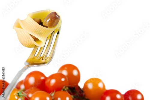 cooked pasta over fork with tomatoes in the background