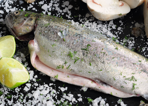 Fresh trout fish with mushrooms, lime and spices