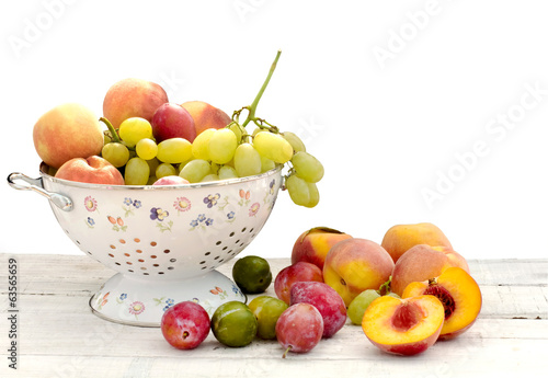 fresh summer fruits inside decorated ceramic colander