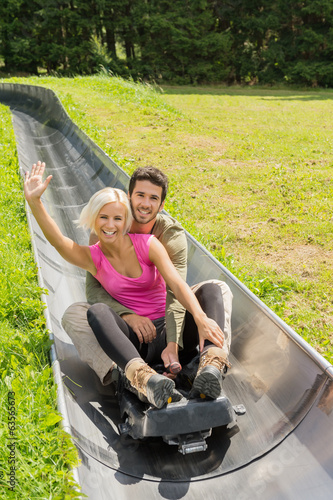Happy Couple Enjoying Summer Sledge