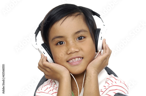 a little sweet girl with headphones listening to music