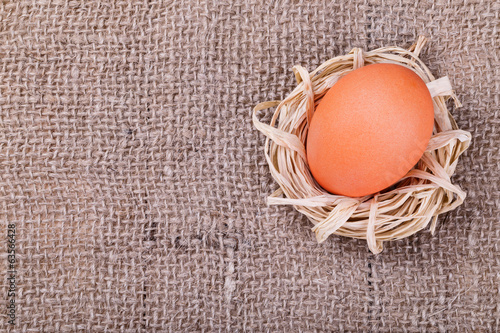Orange egg on burlap background