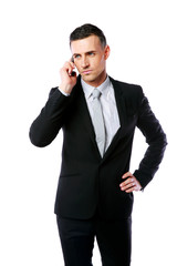 Handsome businessman talking on the phone over white background