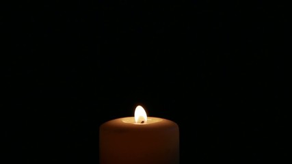 Candle goes on black background. Slow motion