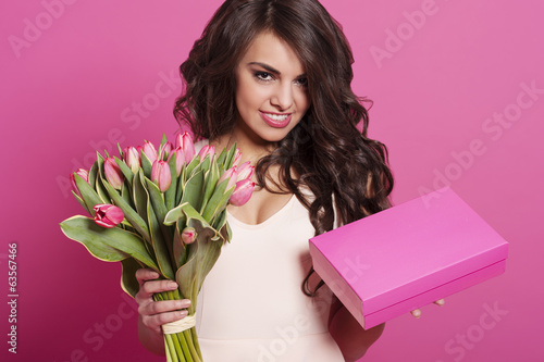Beautiful young woman with spring bouquet and gift box .