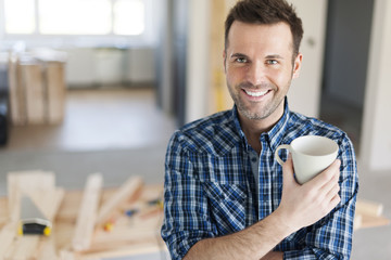 Portrait of man drinking coffee on construction side