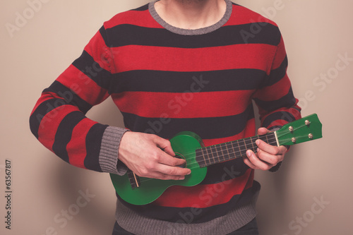 Man in striped jumper playing ukulele