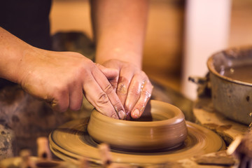 Close-up of hands making pottery on a wheel