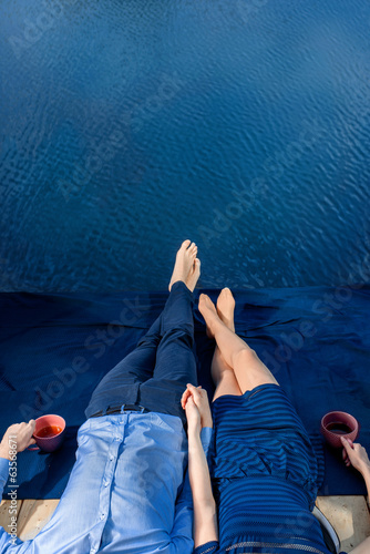 couple lying on terrace near water